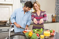 Man and woman making salad, smiling (thumbnail)
