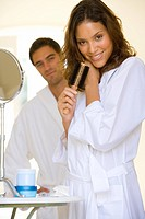 Young couple in bathrobes, woman with hairbrush, smiling, portrait differential focus (thumbnail)