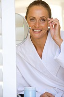 Woman in bathrobe plucking eyebrows, smiling, portrait