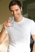 Young man with glass of water, smiling, portrait, close-up
