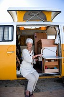 Senior woman making tea in camper van, smiling, portrait (thumbnail)