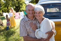 Senior couple embracing by camper van, smiling, portrait