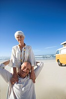 Senior couple on beach by camper van, smiling, portrait