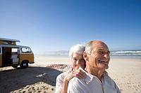 Senior couple on beach by camper van, woman behind man, smiling, close-up