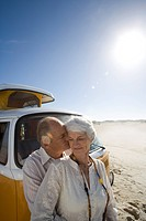 Senior couple on beach by camper van, man kissing woman on cheek, close-up lens flare