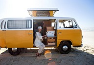 Senior woman making tea in camper van on beach, smiling, portrait lens flare