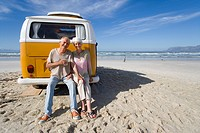 Senior couple sitting on back of camper van on beach, smiling, portrait
