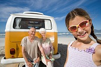 Girl 7-9 wearing sunglasses on beach by grandparents on back of camper van, smiling, close-up (thumbnail)
