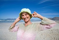 Senior woman holding hat on head on beach, smiling, portrait, close-up
