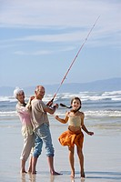 Girl 7-9 by grandparents fishing on beach, smiling, portrait
