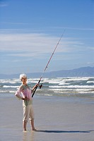 Senior woman fishing on beach, smiling, portrait