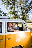 Senior couple in camper van, smiling, portrait of man