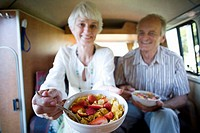 Senior couple eating breakfast in back of camper van, smiling, close-up of bowl differential focus