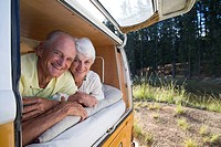 Senior couple lying in back of camper van, smiling, portrait, close-up