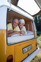 Senior couple lying in back of camper van, smiling, portrait, low angle view