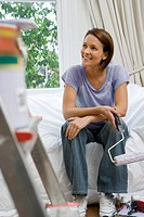 Young woman on sofa with paint roller, paint pot on ladder in foreground differential focus