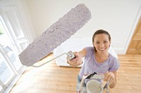 Young woman on ladder painting with paint roller, elevated view differential focus