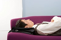 Businessman using briefcase as pillow, asleep on sofa, close-up