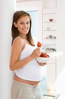 Young pregnant woman with bowl of strawberries, smiling, portrait, side view (thumbnail)