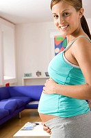 Young pregnant woman with hands on stomach, smiling, portrait, side view