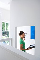 Young woman with paint tray painting wall with roller, smiling, portrait