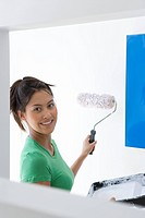 Young woman with tray and roller painting wall, smiling, portrait