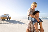 Boy 6-8 on father's shoulders on beach, smiling, portrait (thumbnail)