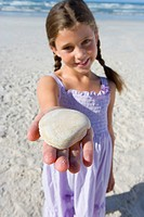 Girl 5-7 with shell on beach, smiling, portrait differential focus