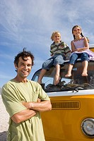 Man on beach with arms crossed by son and daughter 5-9 on roof of camper van, portrait, low angle view
