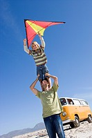 Boy 6-8 standing on father's shoulders with kite on beach, camper van in background, low angle view