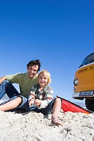 Father and son 6-8 on beach with kite by camper van, smiling, portrait, low angle view