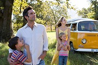 Parents embracing son and daughter 5-9 in field by camper van, low angle view