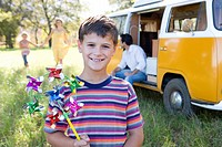 Boy 6-8 with pinwheel, family by camper van in background, smiling, portrait