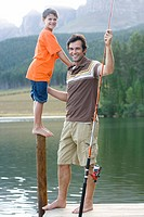 Father with fishing rod by son 6-8 on pole on jetty, smiling, portrait