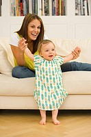 Young pregnant woman on sofa holding hands of baby girl 9-12 months, smiling, portrait