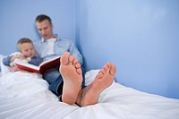 Father reading to son 4-6 in bed, close-up of father's feet differential focus
