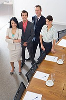 Businessmen and women by conference room table, smiling, portrait, elevated view