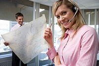 Businesswoman wearing headset in office by colleague with blueprint, smiling, protrait, close-up