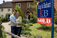 Young couple embracing outside house with 'sold' sign, smiling, portrait