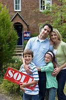 Family of four outside house, boy 8-10 with 'for sale' sign, smiling, portrait