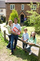 Family of four by fence by house, father holding 'sold' sign, smiling, portrait