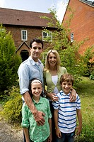 Family of four outside house, smiling, portrait