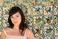 Young woman by decorated tiles, smiling, portrait