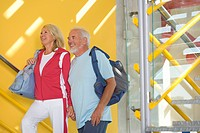 Senior couple walking up steps with gym bags, smiling, side view