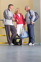 Senior couple in conversation with man, all with gym bags, low angle view