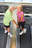 Senior man and woman on treadmills, in conversation, elevated view