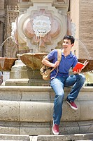 Man on edge of fountain with book, smiling