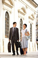 Businessman smiling at wife with luggage, low angle view