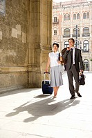 Businessman and woman with luggage outdoors, portrait