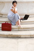 Young woman with briefcase using laptop computer on steps outdoors, smiling, portrait